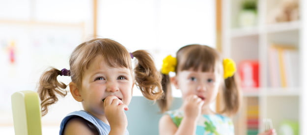 Two young girls eating vegetables