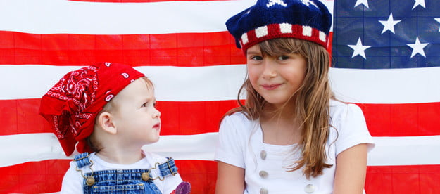 Two kids sitting in front of a U.S. flag