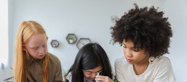 Three young girls using a microscope