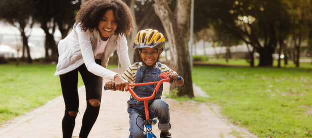 Woman with young son on a bike in a park
