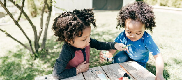 Two toddlers playing outside