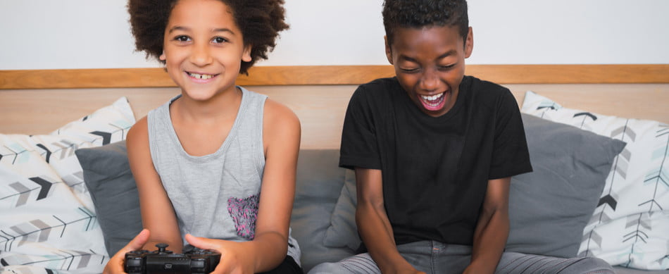 Two kids having fun playing video games on the couch
