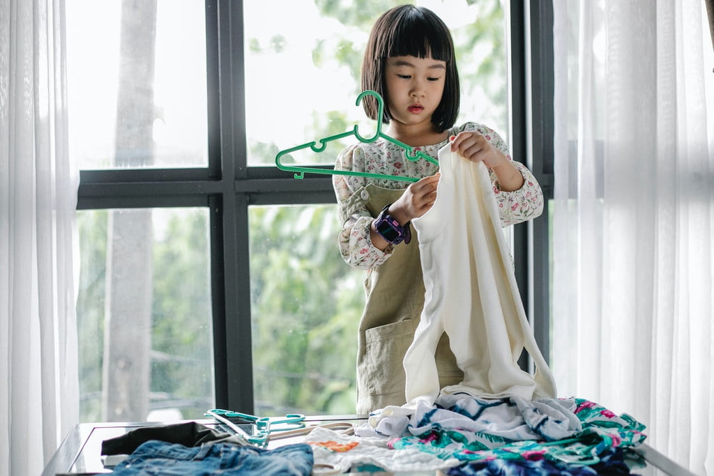 little girl putting up sweater