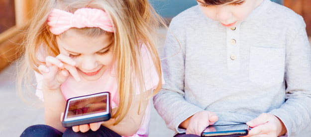 two kids playing on phones
