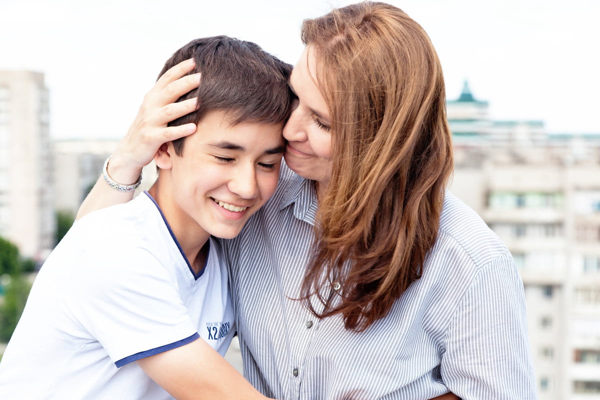 A mom embraces her teenaged son