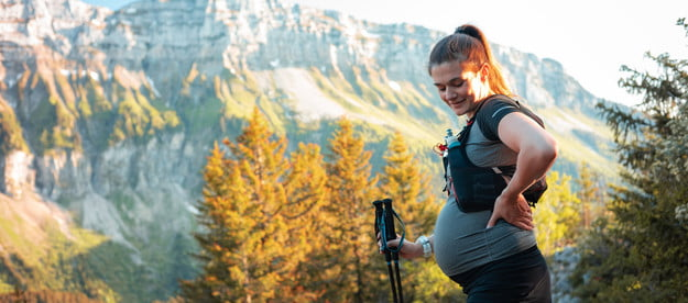 Pregnant woman hiking on a trail