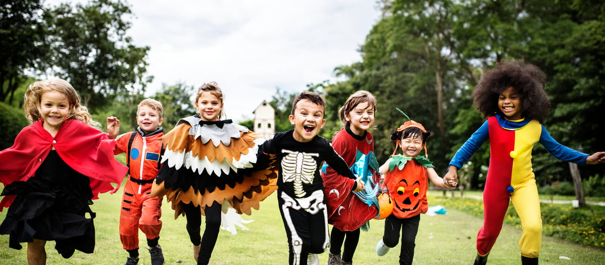 A group of kids in Halloween costumes running outside.