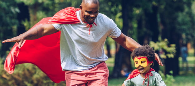 A father and son playing super heroes in the yard.
