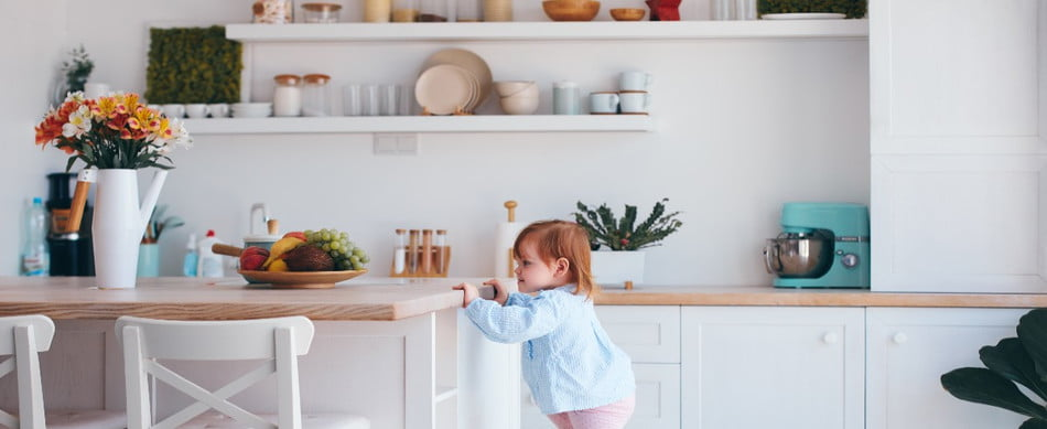 A toddler using a step stool in a kitchen