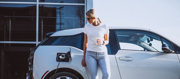 Woman standing with a coffee while her electric car charges