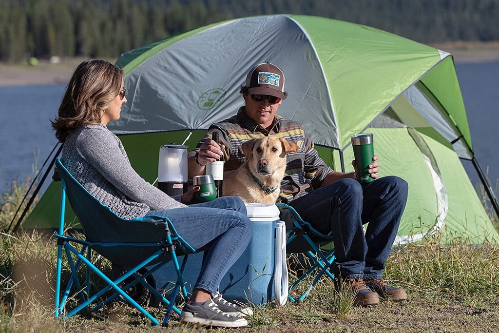 woman, man, and dog sitting in front of a tent