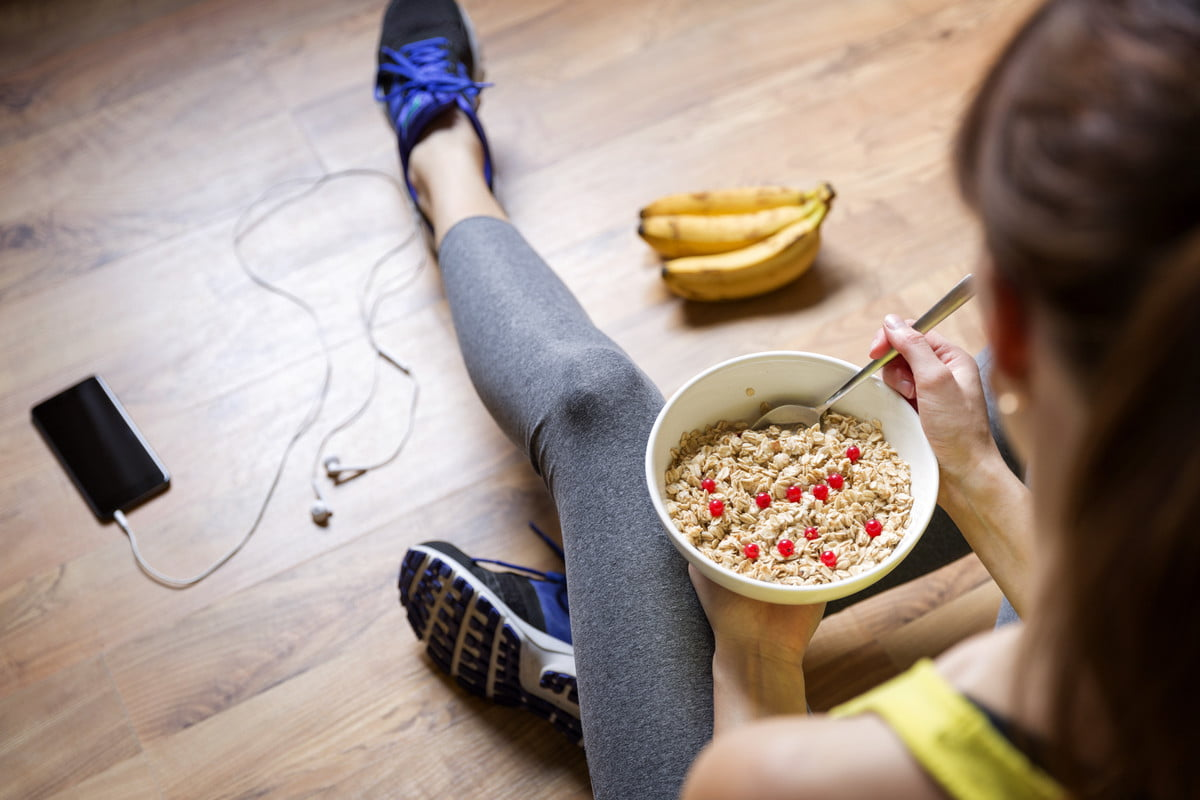 Woman sitting on floor while eating cereal.