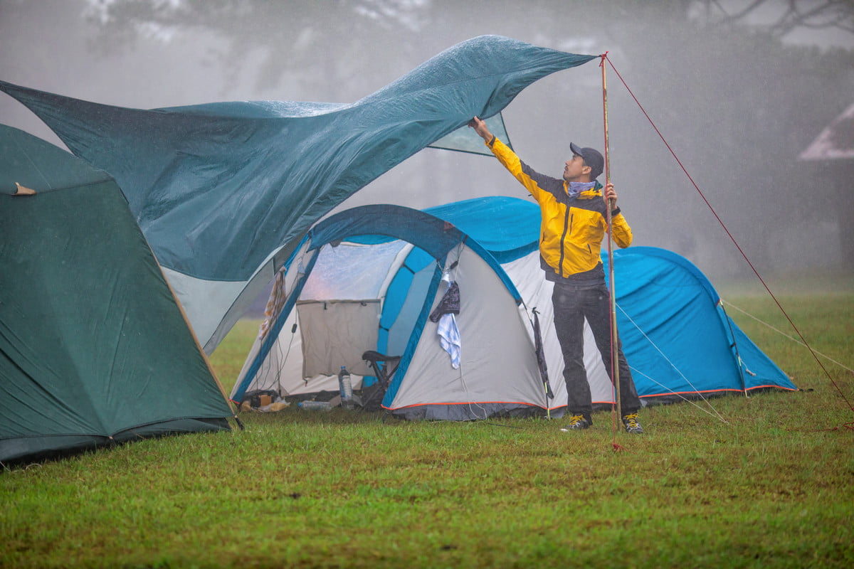 Camper fixing a tent in the rain