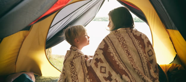 sleeping bag air mattress mom and son camping in a tent