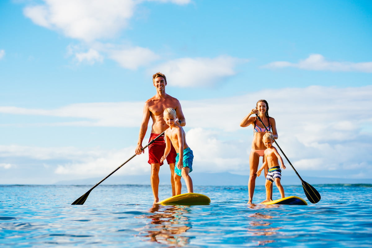 man and woman with children on standup paddleboards
