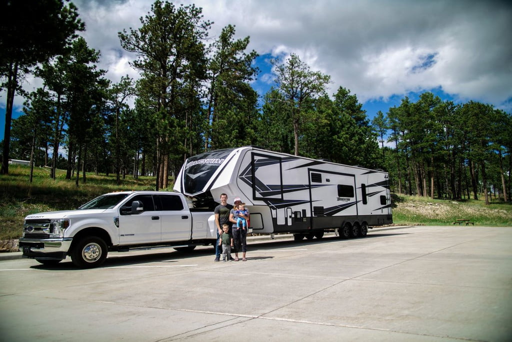family standing beside their pickup truck and travel trailer
