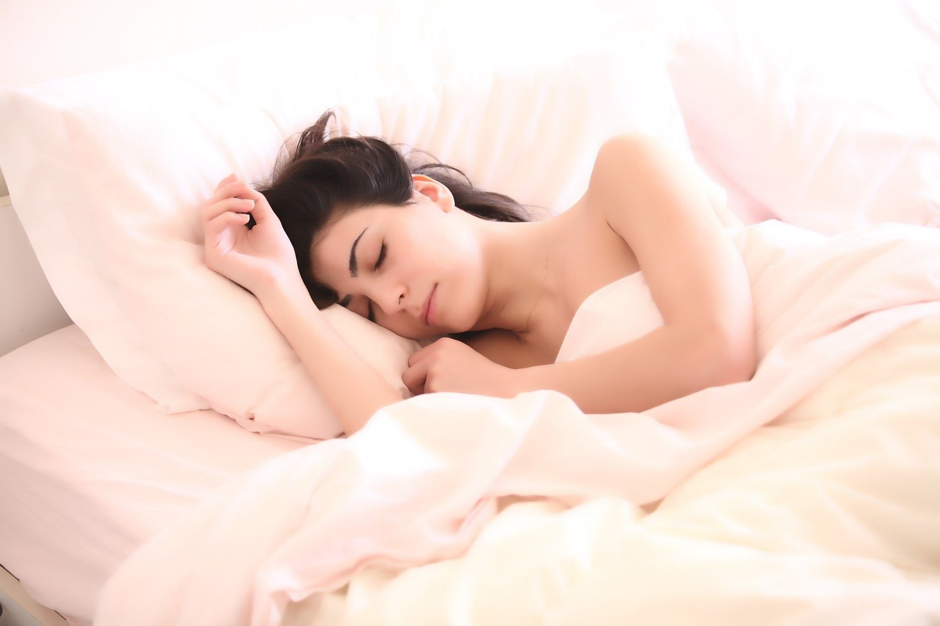 woman sleeping with a pillow in bed