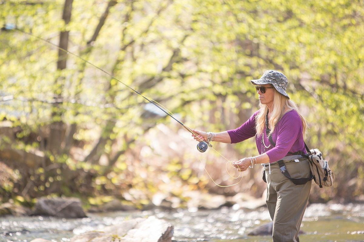woman in a stream fly fishing