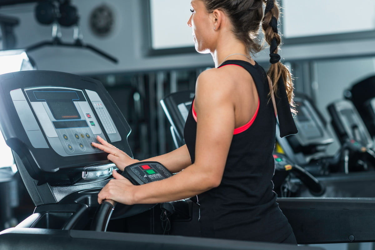 A woman begins a treadmill workout
