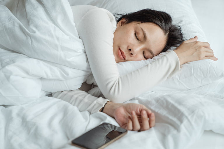 Woman Sleeping On Bed Next To Smart Phone