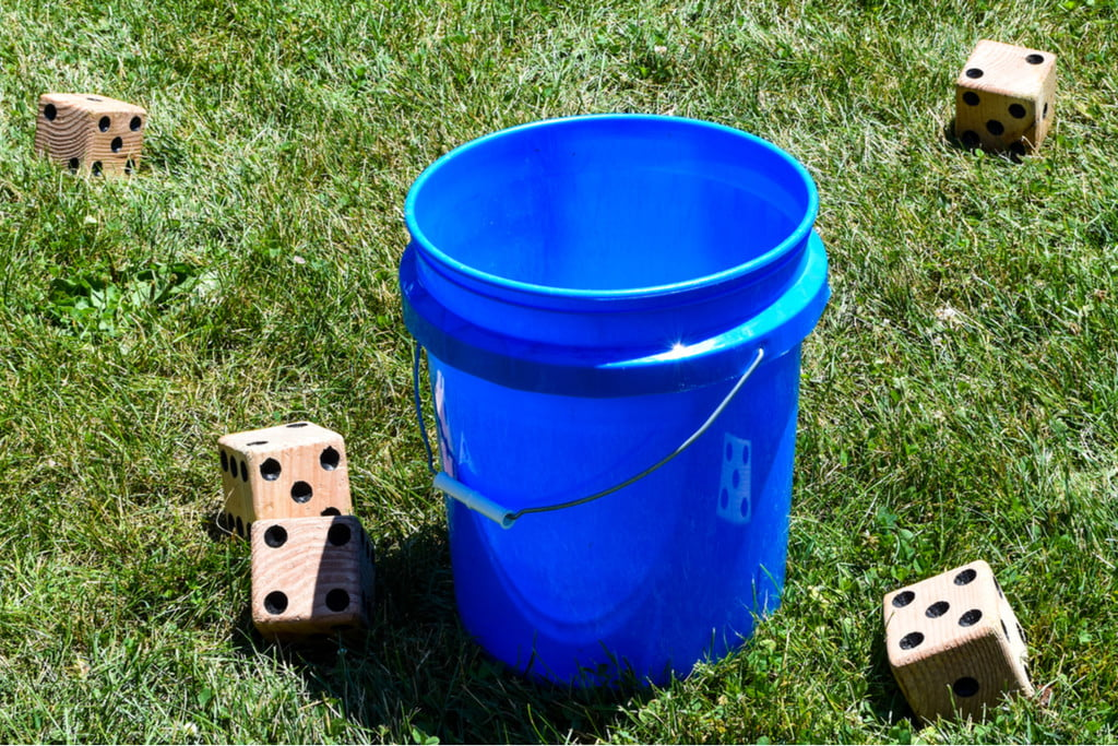 yard dice on a lawn with a blue bucket